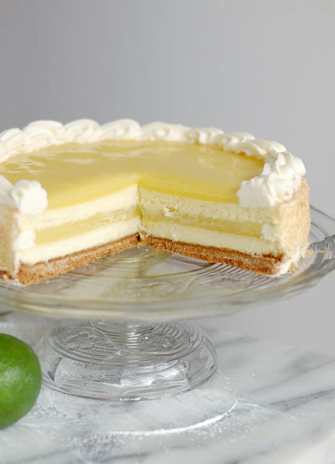 a partially cut lime layered cheesecake on a glass cake stand