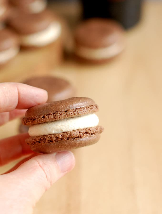 a hand holding a chocolate macaron with baileys irish cream filling
