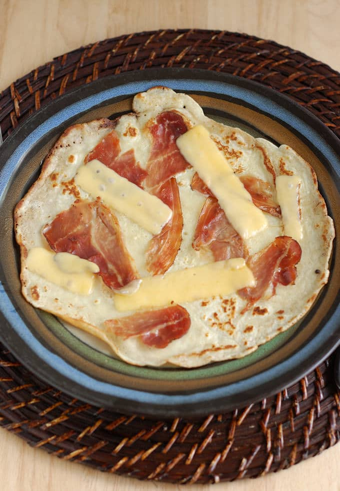 a savory Dutch Pancake with Speck and Gouda on a plate