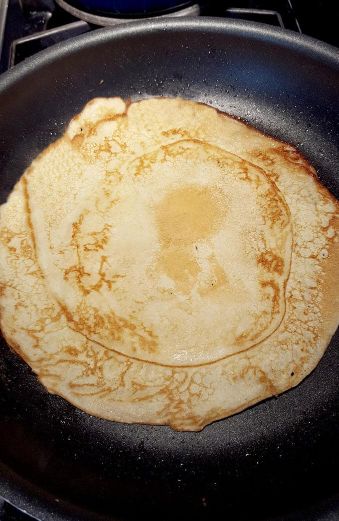 a large dutch pancake in a pan, browned side up
