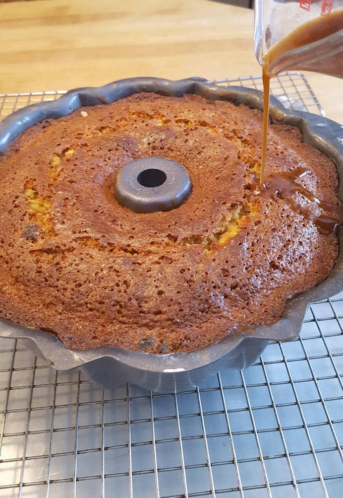 a bundt cake on a cooling rack with syrup being poured over the top