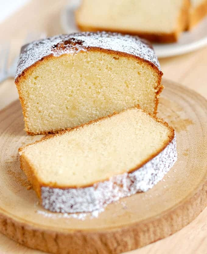 a sliced honey pound cake on a wooden cake plate