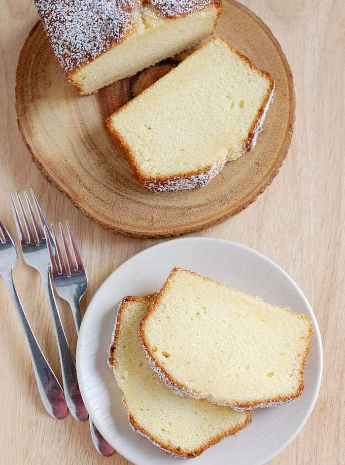 An overhead view of two slices of cake on a white plate and a slice cake on a wooden cake stand.