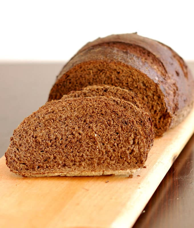 sliced loaf of sourdough pumpernickel bread on a cutting board