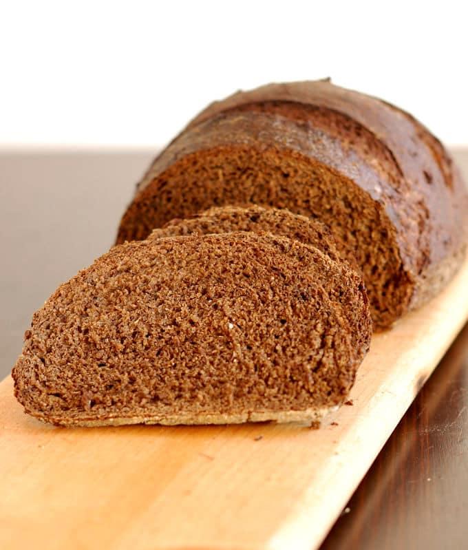 sliced loaf of sourdough pumpernickel bread on a cutting board
