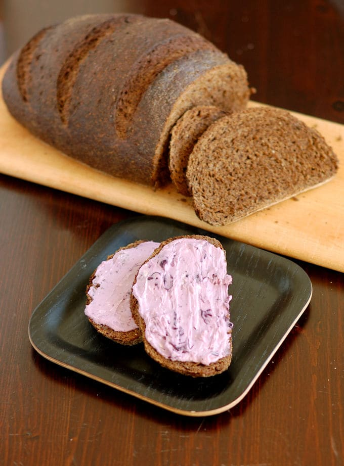two slices of pumpernickel rye bread with blueberry cream cheese in foreground, loaf in background
