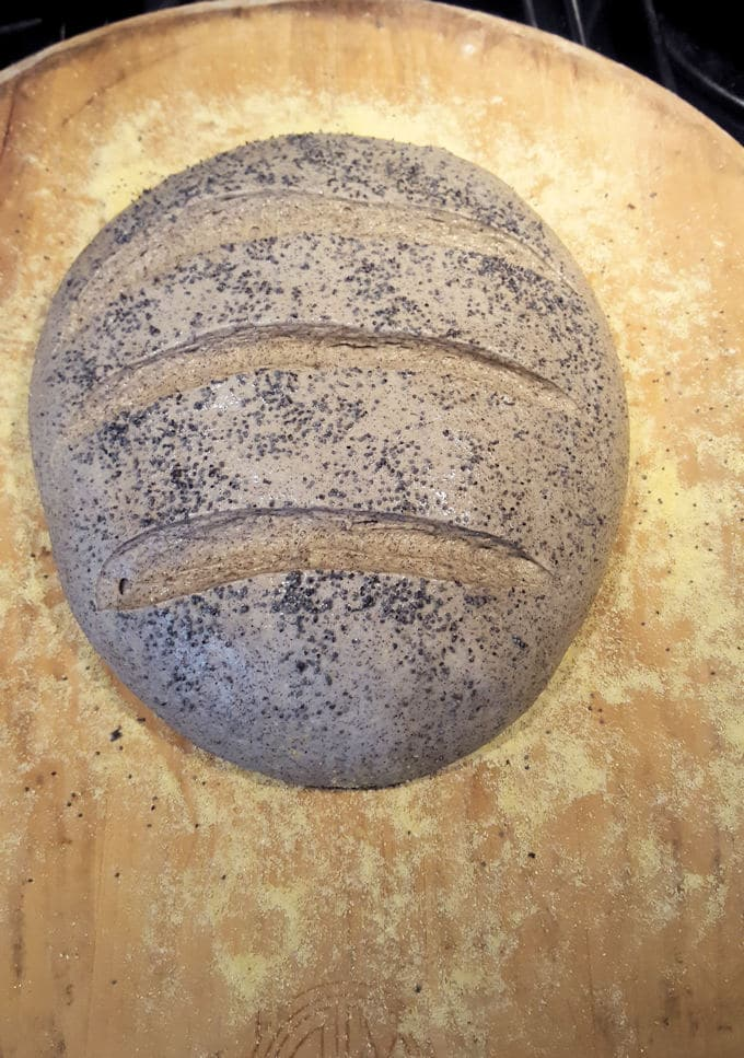 a loaf of unbaked guinness buckwheat bread on a wooden peel