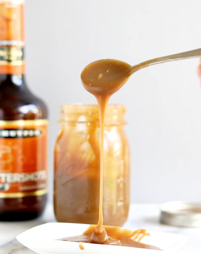 a spoon drizzing butterscotch sauce onto a plate