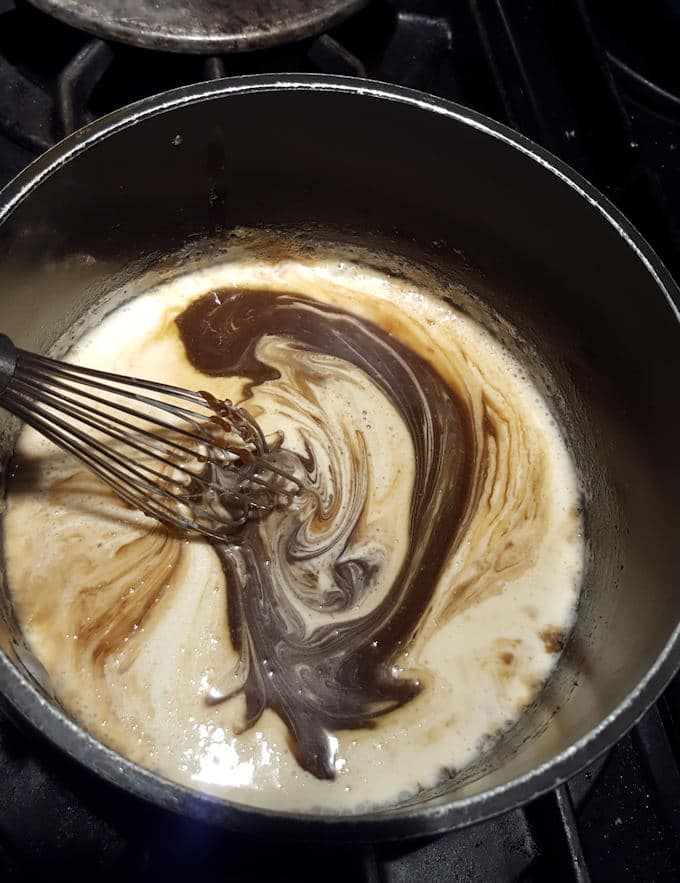 photos shows a pot with a  whisk adding cream into butterscotch sauce