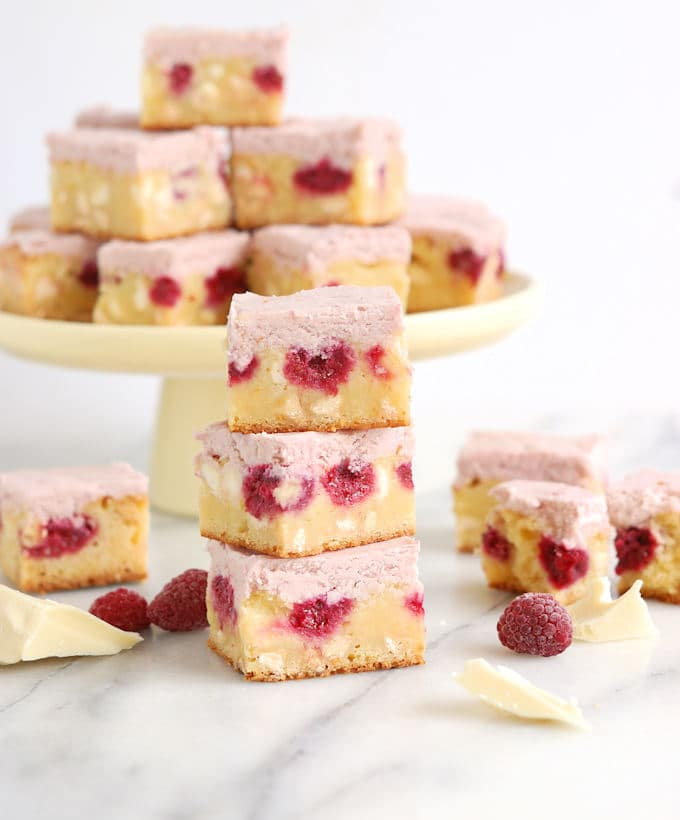 a stack of white chocolate brownies with raspberries on a marble surface