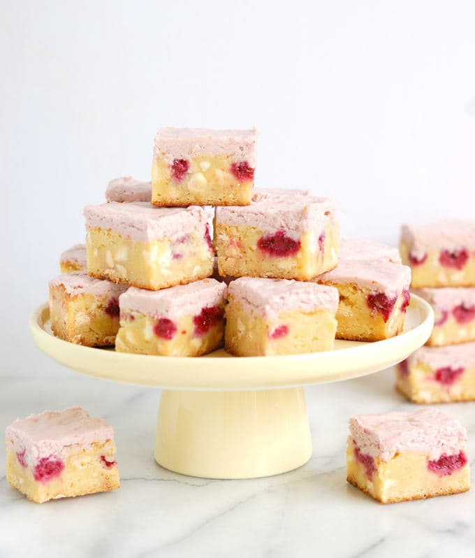 a tray of white chocolate brownies with raspberries and raspberry frosting