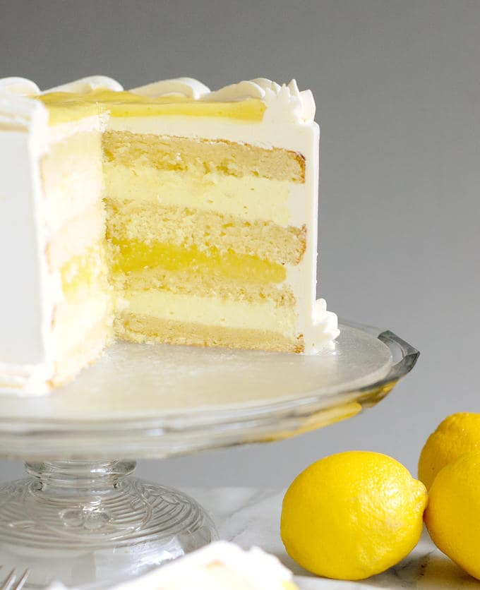 A lemon layer cake on a glass cake stand.