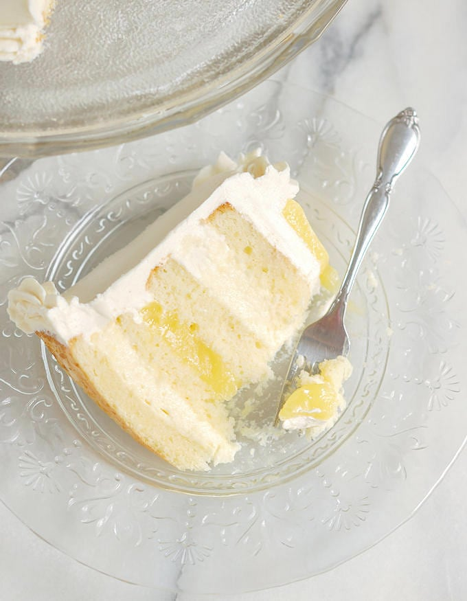 a partially eaten slice of lemon mousse layer cake on a glass plate with a fork