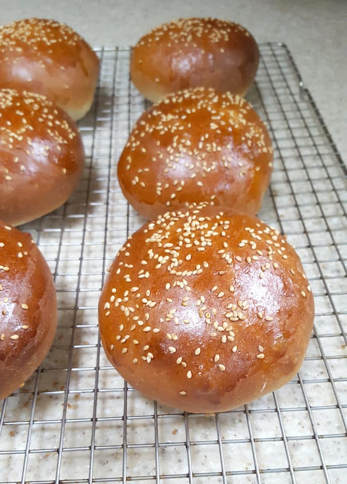 Golden brown whole wheat hamburger buns cooling on a rack
