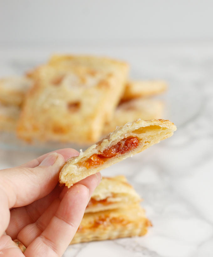 a hand holding a cherry almond hand pie