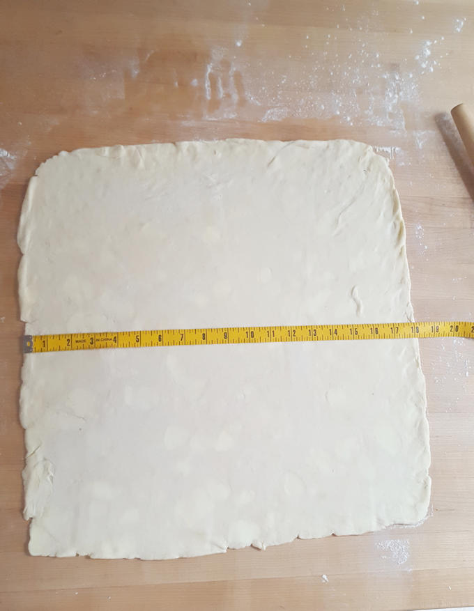a pie of roll dough with a measuring tape.