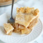 a slice of glazed apple pie on a white plate with a fork