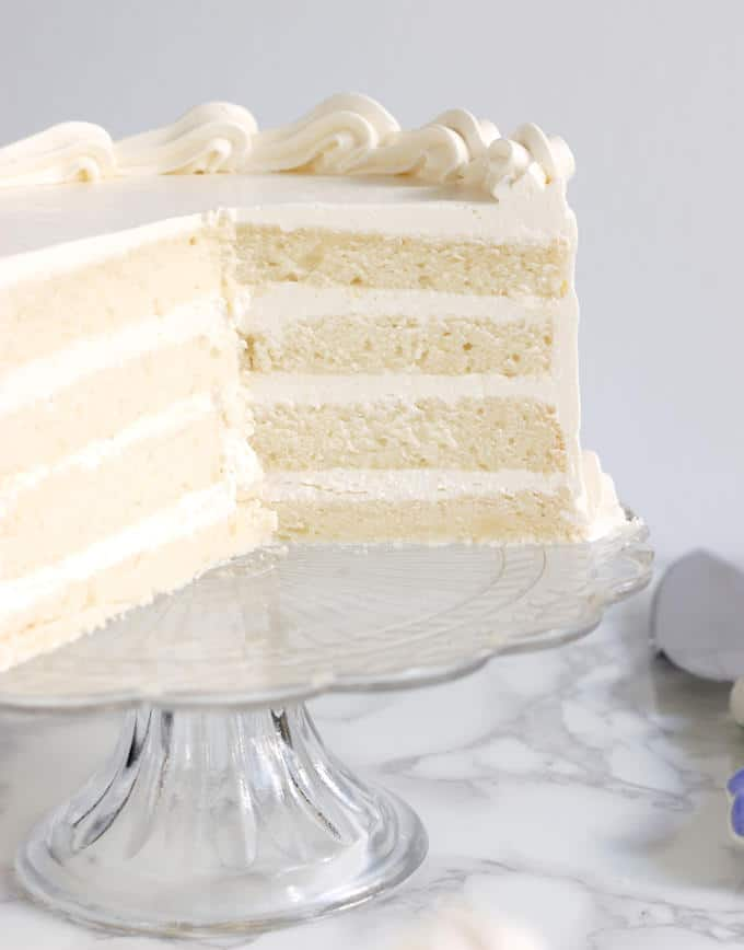 An cross section of a four layer velvety soft white cake 1/2 on a glass cake stand.