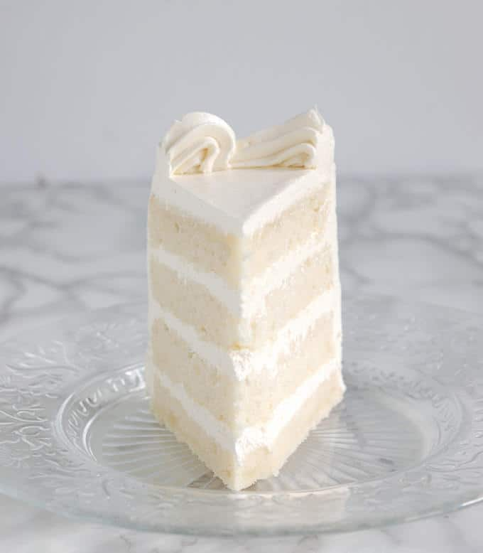 A slice of four layer velvety soft white cake with white icing on a glass plate.