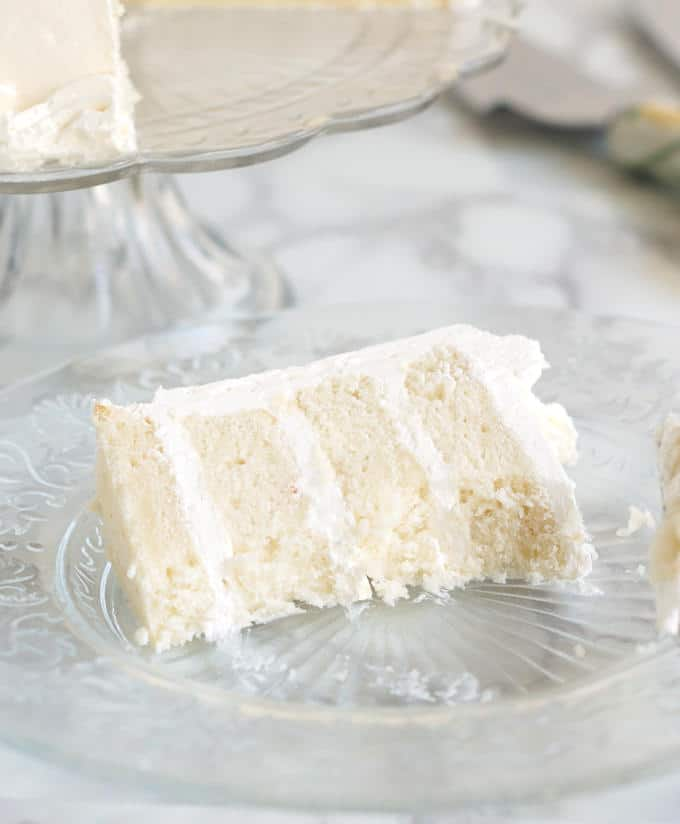 A half-eaten slice of four layer velvety soft white cake on a glass plate