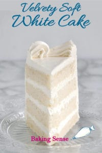 A slice of 4 layer white cake with white icing on a glass plate.