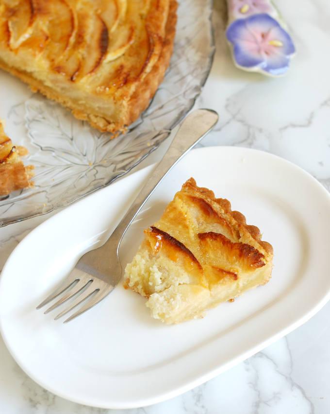 a half eaten slice of Apple Frangipane Tart on an oval plate with a fork