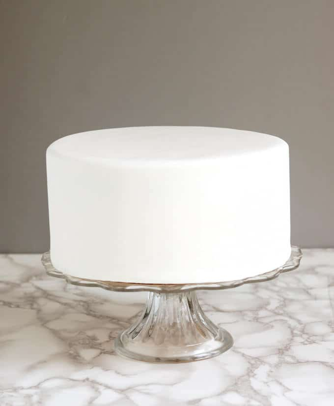 A white cake covered in rolled fondant on a glass cake plate