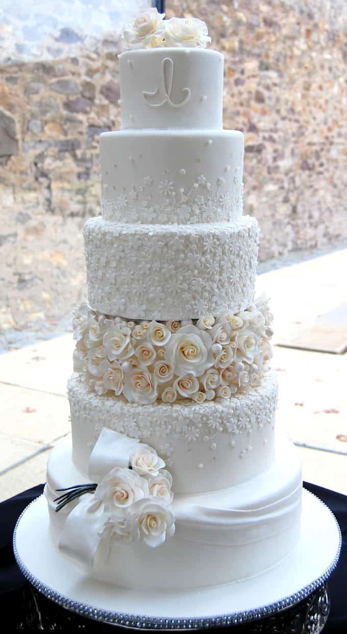 a five tier wedding cake covered with rolled fondant