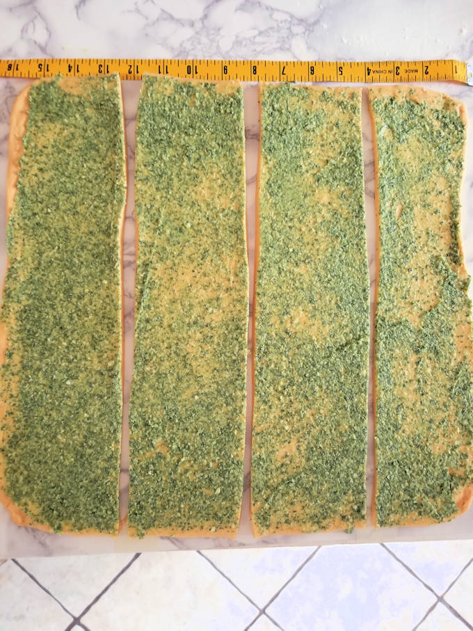 strips of pumpkin dough covered with sage pesto