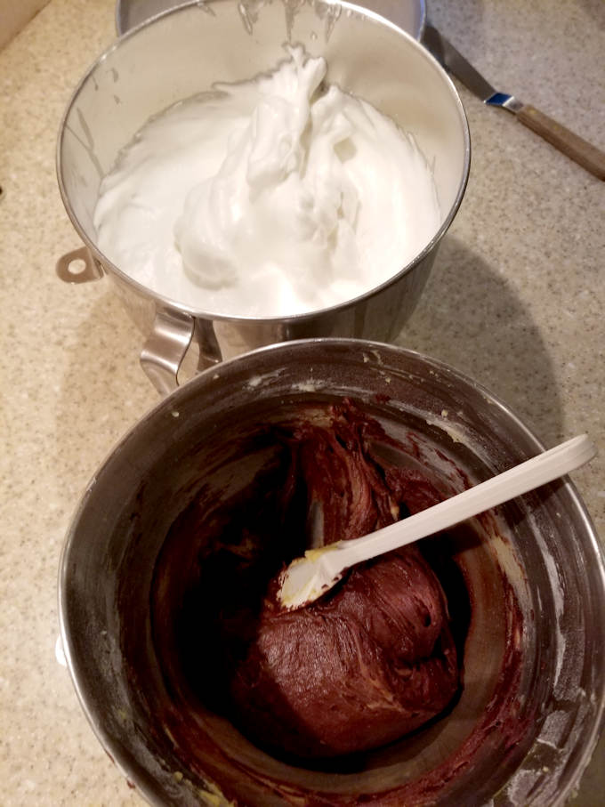 a bowl of chocolate cake batter and a bowl of whipped egg whites for making sacher torte