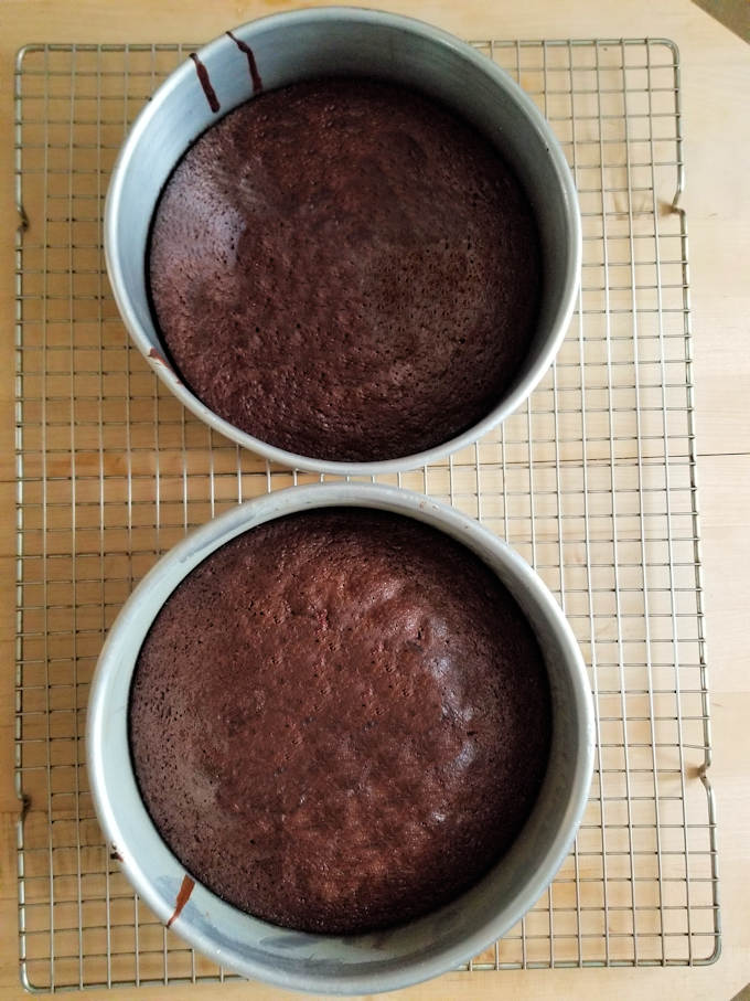 two chocolate cakes cooling on a rack.