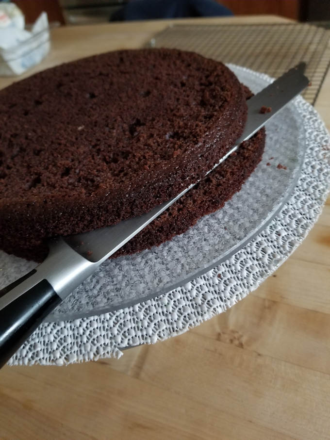 splitting a chocolate cake layer into two smaller layers.