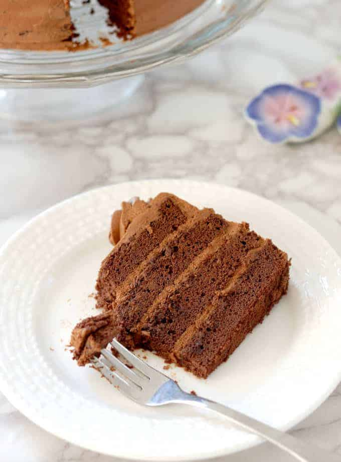 a partially eaten slice of chocolate genoise filled with chocolate cream