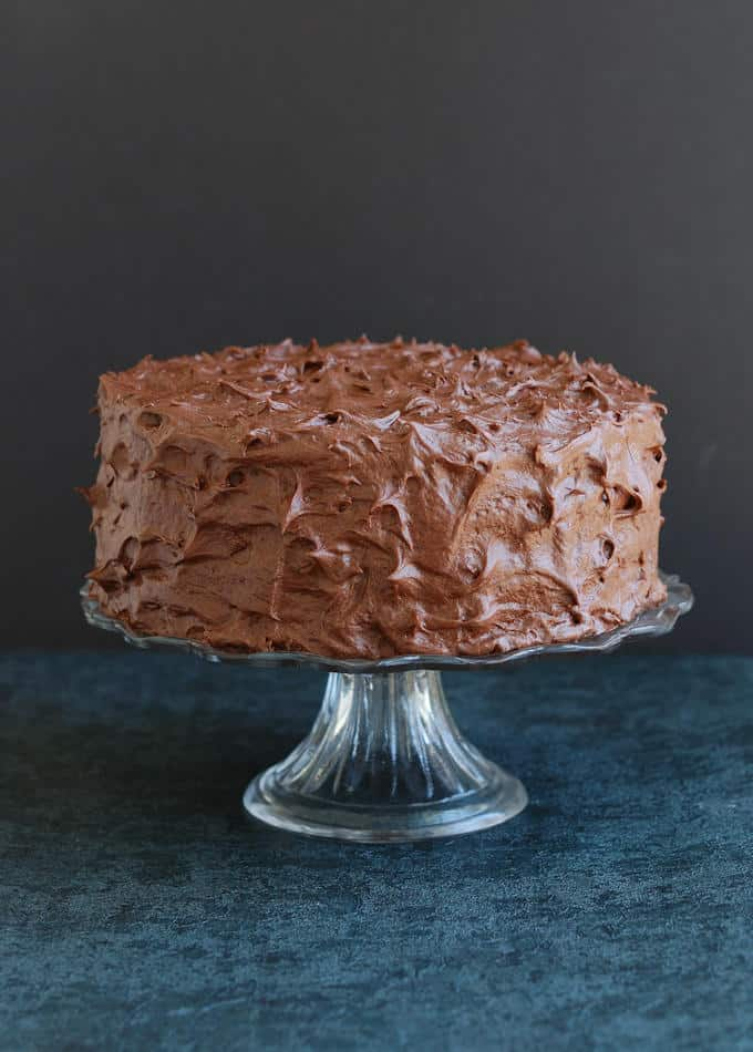an old fashioned chocolate cake on a cake stand