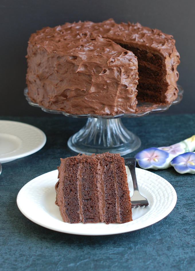 a slice of chocolate cake and a whole cake in the background