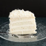 a slice of Snow White Coconut Layer Cake on a glass plate