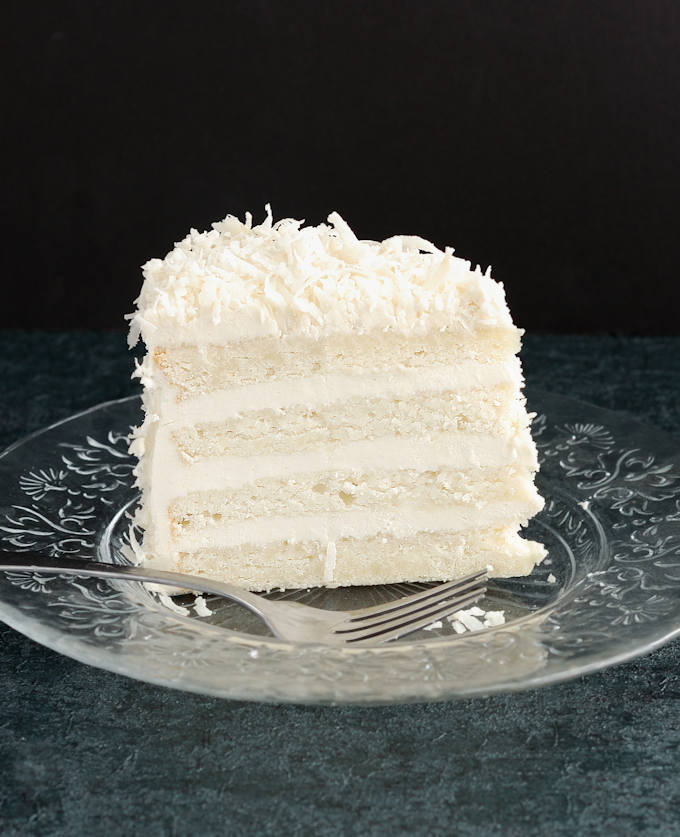 a slice of White Coconut Cake against a black background