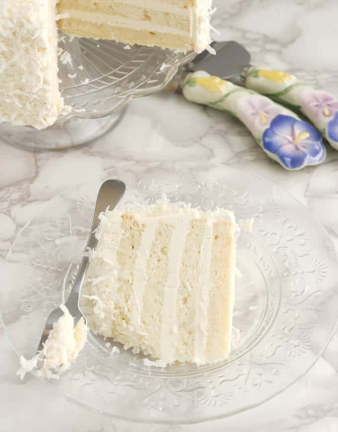 a slice of Snow White Coconut Layer Cake on a glass plate with a fork