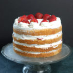 a four layer strawberry and cream cake on a glass cake stand