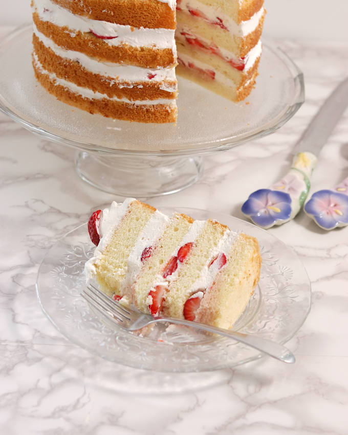 a slice of strawberry cake on a glass plate