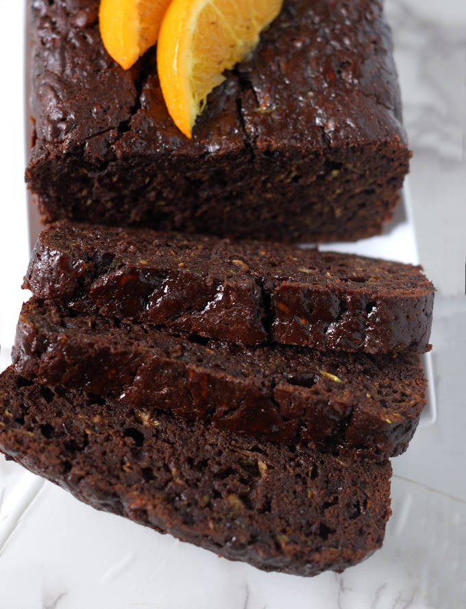 a sliced loaf of chocolate orange zucchini bread on a tray