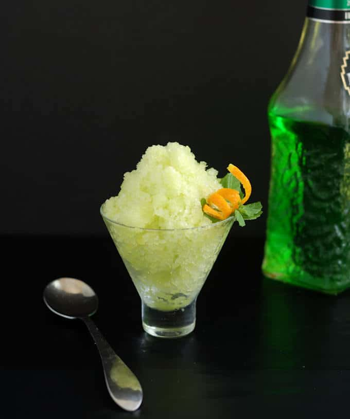 a bowl of green melon granita with an orange twist against a black background