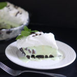 a slice of mint chocolate chip ice cream pie on a white plate