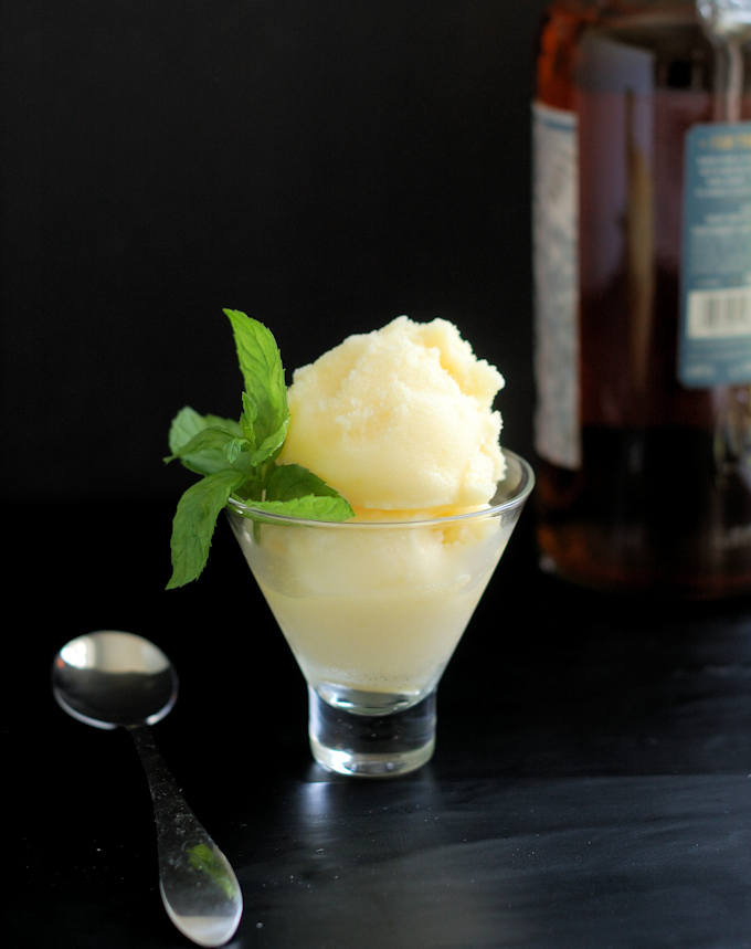 a glass filled with homemade pineapple sorbet and a sprig of mint