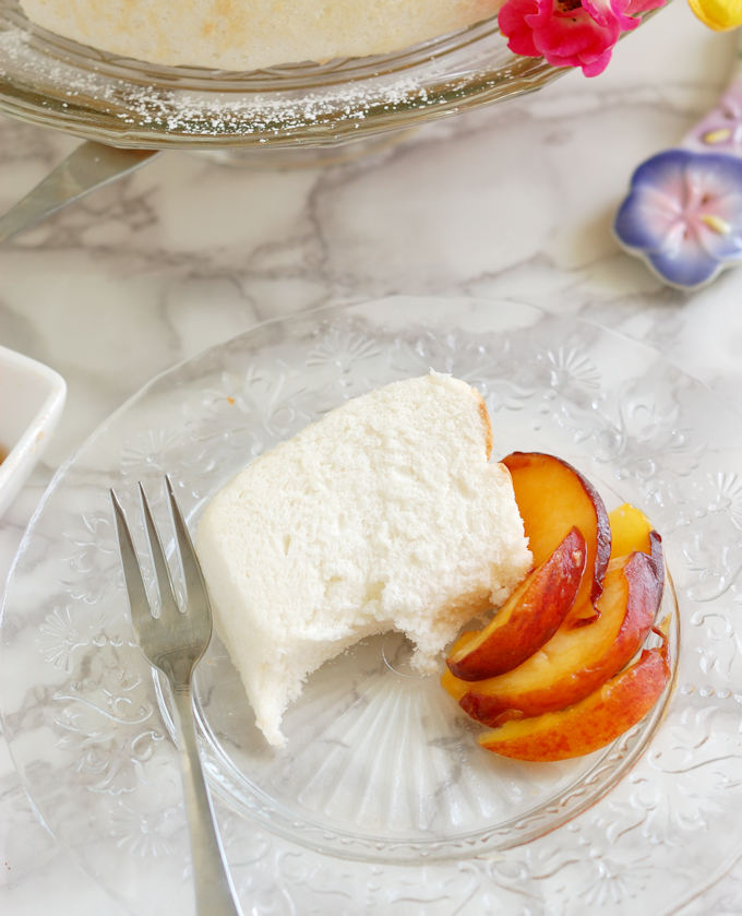 a half eaten slice of angel food cake on a glass plate with a fork and slices peaches