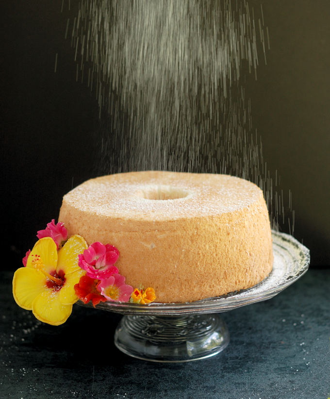 an angel food cake on a glass cake stand is being showered with powdered sugar.