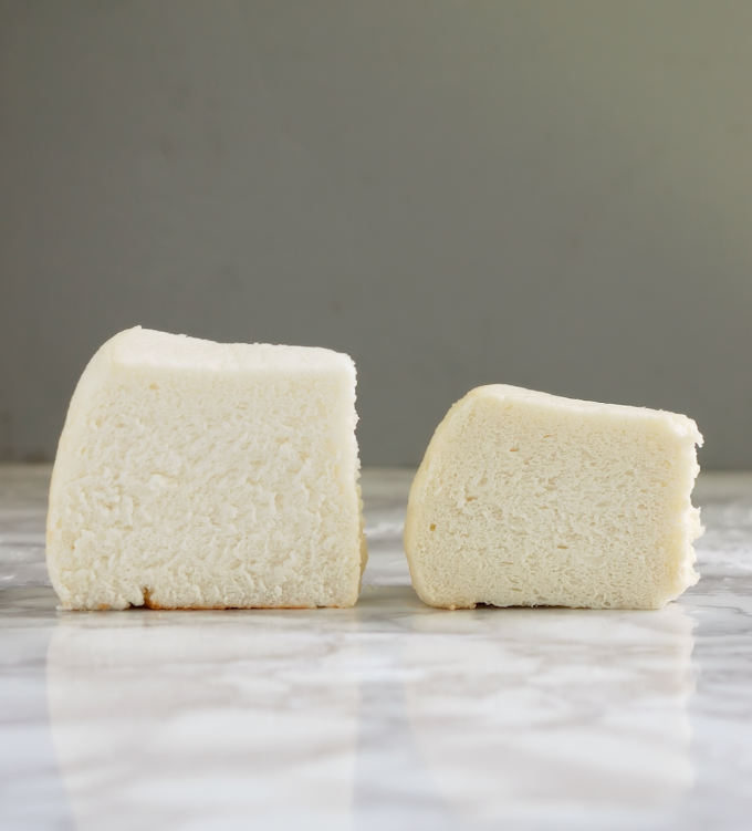Two slices of angel food cake on a marble table.
