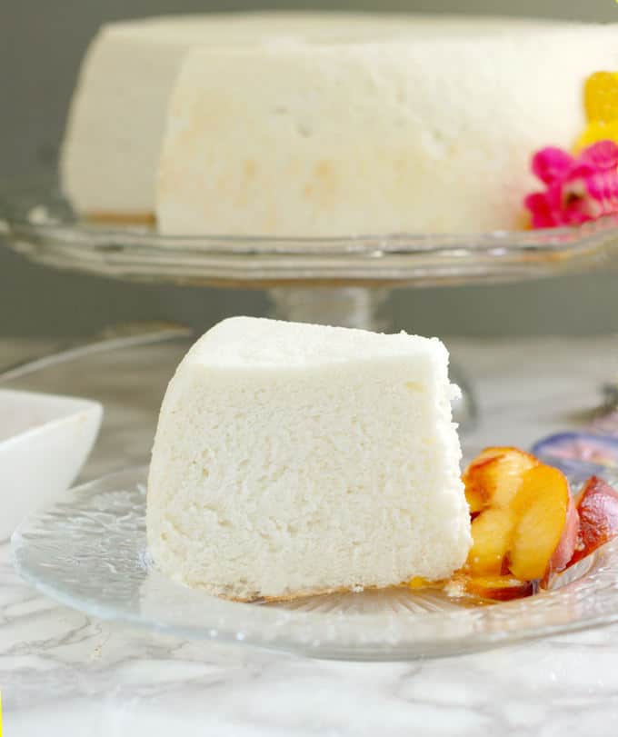 a slice of angel food cake on a glass plate with fresh peach slices. A whole cake is on a stand in the background