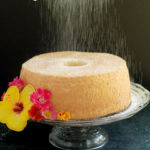 an angel food cake on a cake stand with text overlay