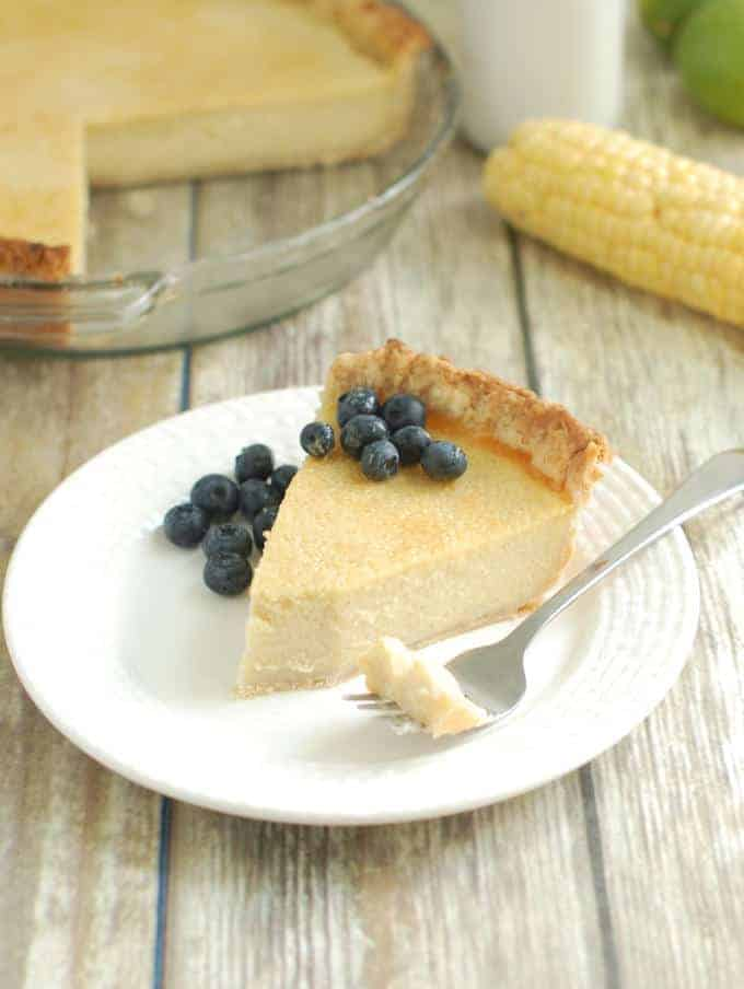 a slice of Sweet Corn Buttermilk Pie served with fresh blueberries